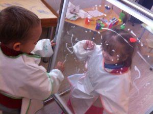 2 children drawing on glas